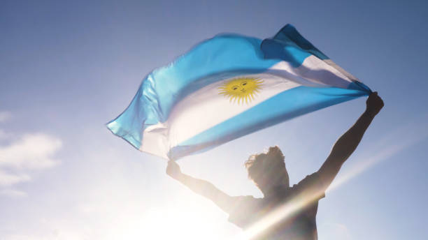 Young man holding argentinian national flag to the sky with two hands at the beach at sunset argentina Young man holding argentinian national flag to the sky with two hands at the beach at sunset Argentina stock pictures, royalty-free photos & images