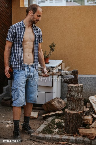 istock Young man holding axe and beer 1294478417