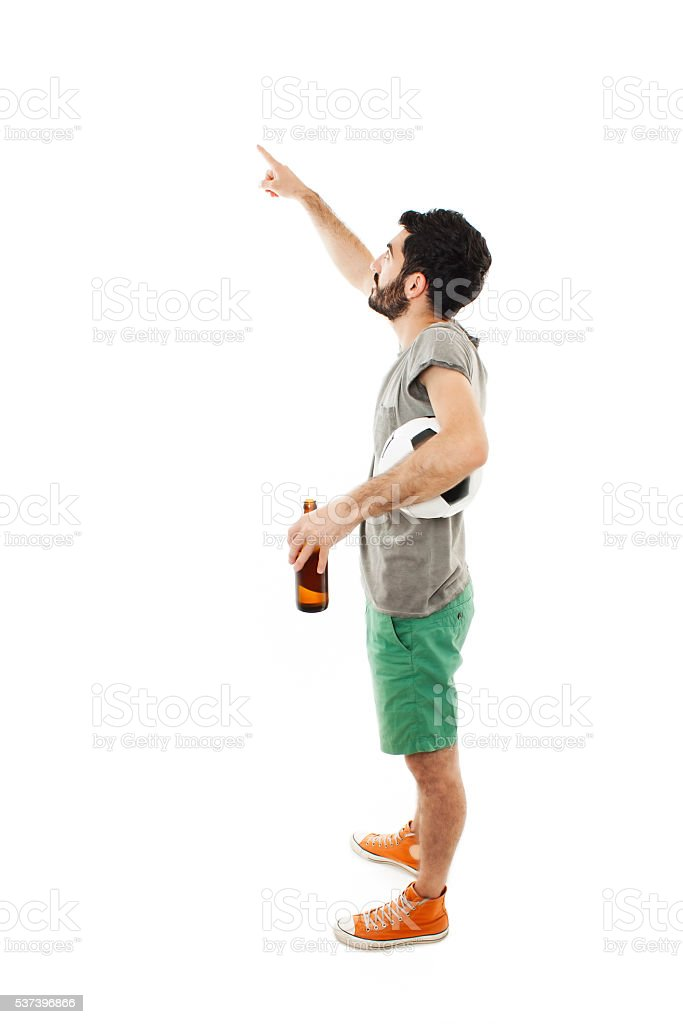 Young man holding ball and beer, pointing stock photo