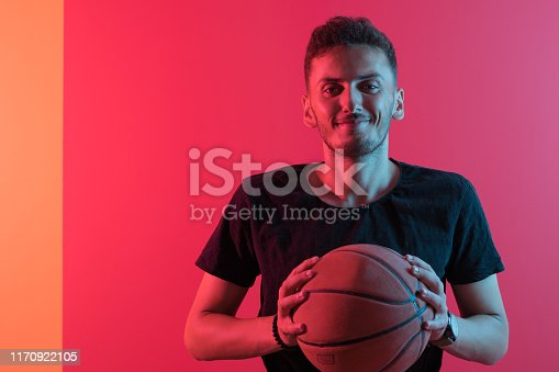 Young man holding basketball ball in hands over colored background.