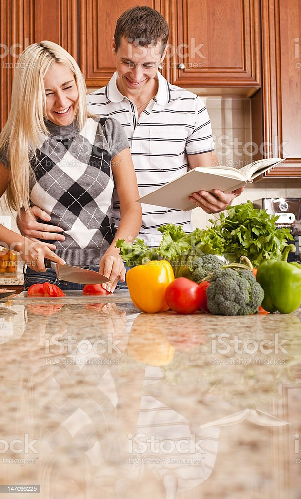 Young Man Holding Book Next to Woman Cutting Tomato royalty-free stock photo