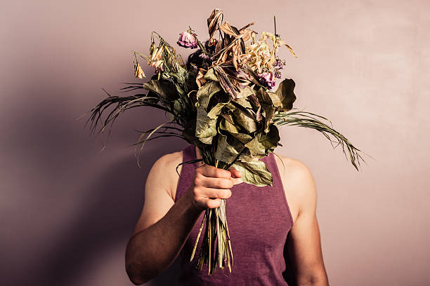 young man holding bouquet of dead flowers - dead plant stock photos and pictures