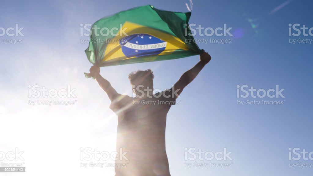Young man holding brazilian national flag to the sky with two hands at the beach at sunset brazil stock photo