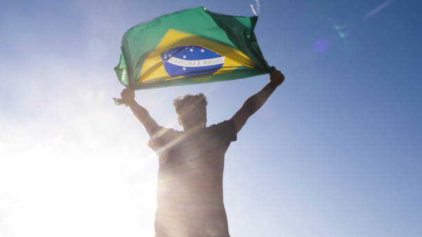 young man holding brazilian national flag to the sky with two hands at the beach at sunset brazil - brasile foto e immagini stock