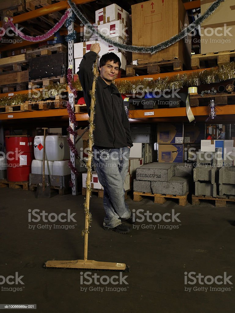 Young man holding broom in warehouse, portrait royalty-free stock photo
