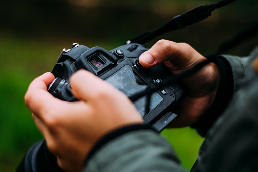 A young man holding a DLSR camera in a natural environment.