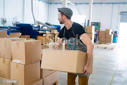 Young man holding carboard boxes stacked at industrial warehouse