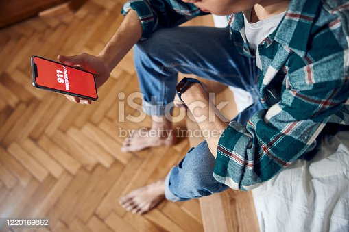 istock Young man holding cellphone with 911 on display 1220169862