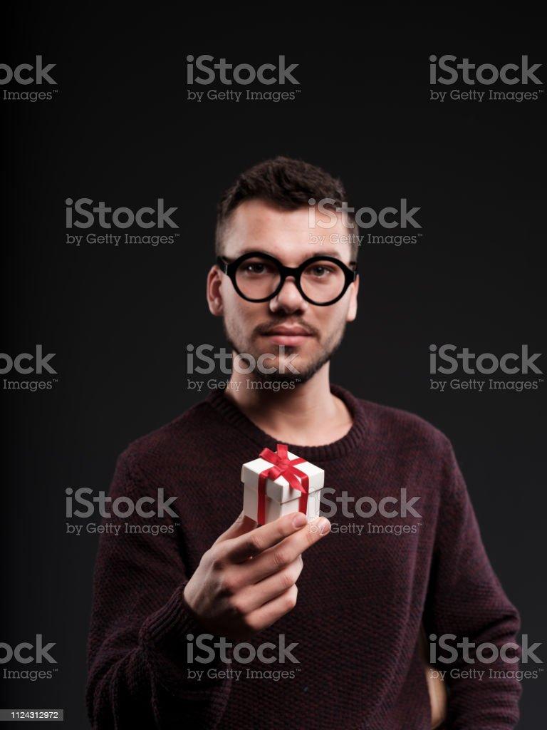 Young man holding christmas gifx box on black background.