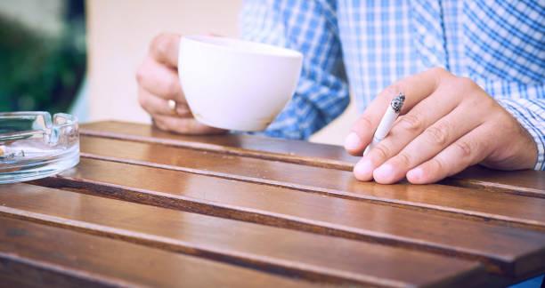 ung man som håller cigarett och kopp kaffe i händer närbild sitter på sommarterrassen i caféet. - coffe with death bildbanksfoton och bilder