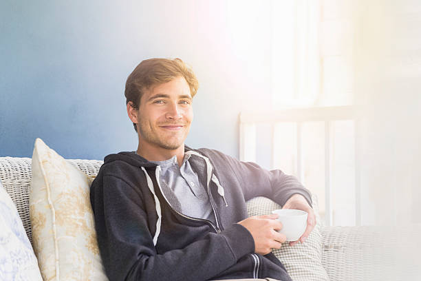Young man holding coffee cup while sitting on sofa stock photo