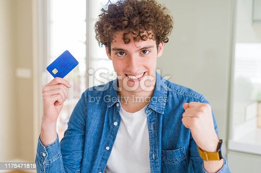 1175468850istockphoto Young man holding credit card screaming proud and celebrating victory and success very excited, cheering emotion 1175471819