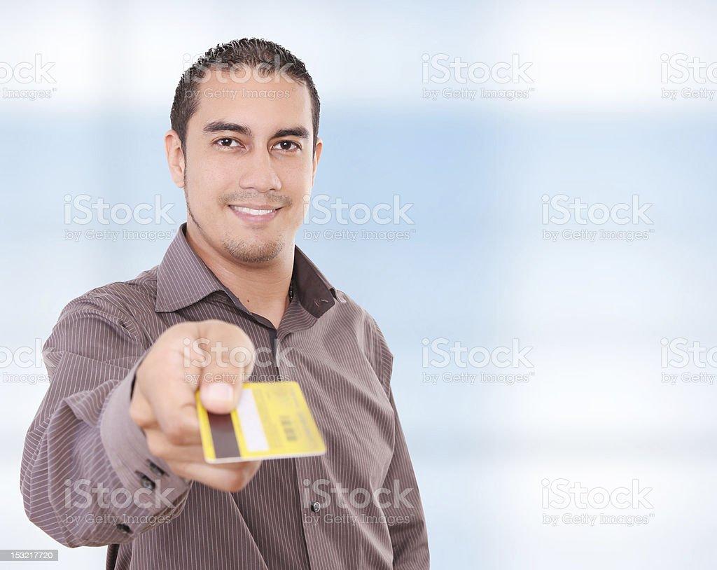 Young man holding credit card towards camera royalty-free stock photo