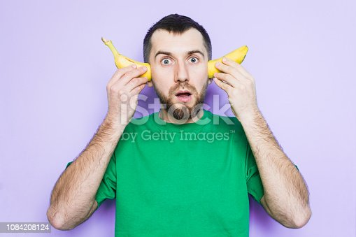 Young bearded man holding cut in half yellow banana on the level of ears, surprised and shocked face expression. Light purple background, copy space.