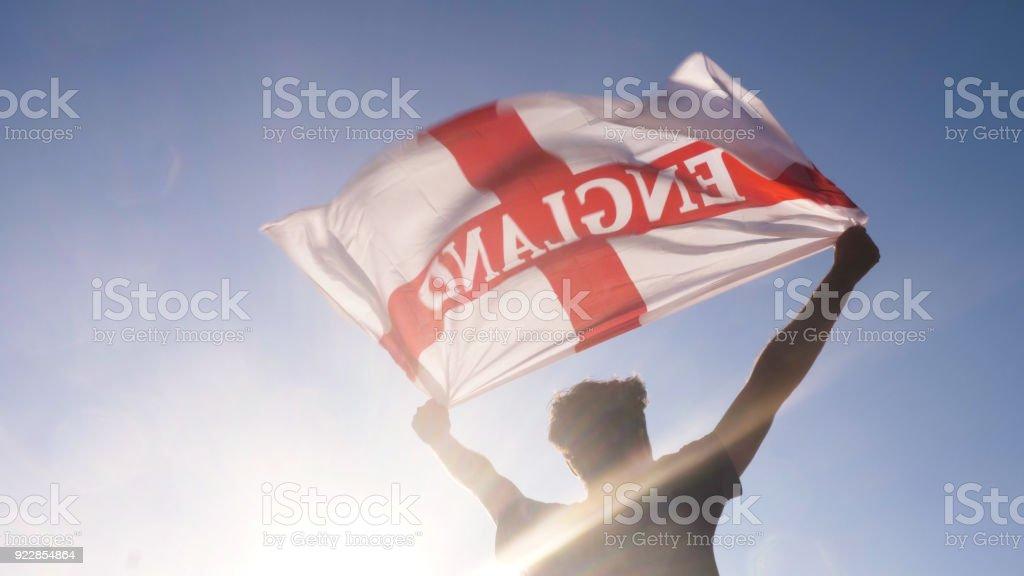 Jeune homme tenant le drapeau national de l'Angleterre vers le ciel avec les deux mains sur la plage au coucher du soleil uk Royaume-Uni - Photo