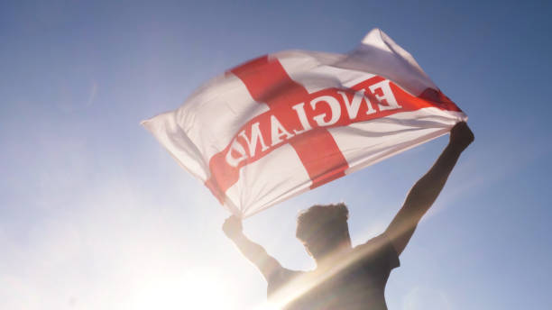 Young man holding england national flag to the sky with two hands at the beach at sunset uk united kingdom stock photo