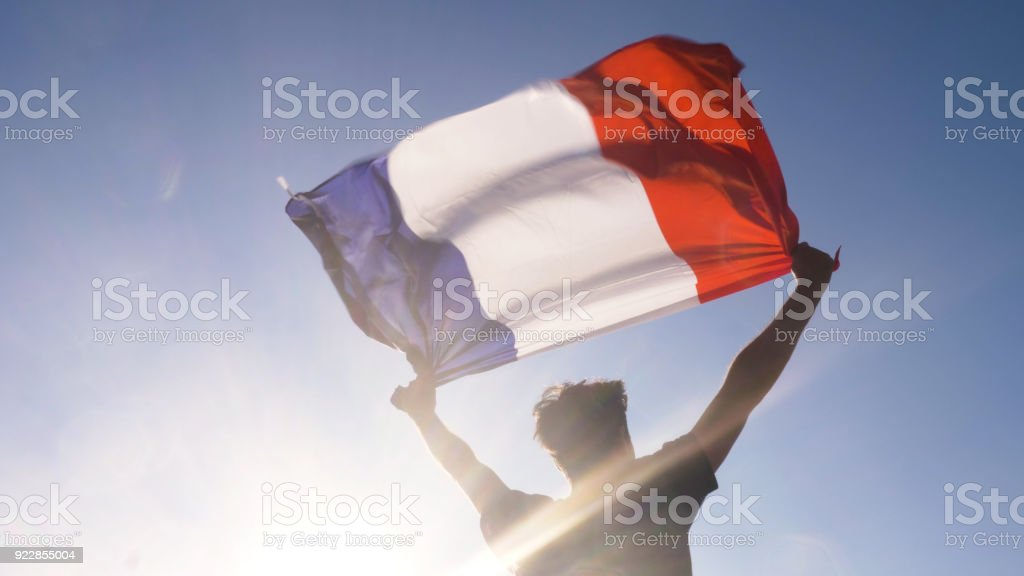 Young man holding french national flag to the sky with two hands at the beach at sunset france stock photo