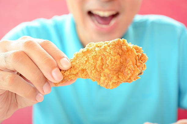 Young man holding  fried chicken leg, about to eat A man with opening mouth about to eat deep fried chicken leg or drumstick fried chicken stock pictures, royalty-free photos & images