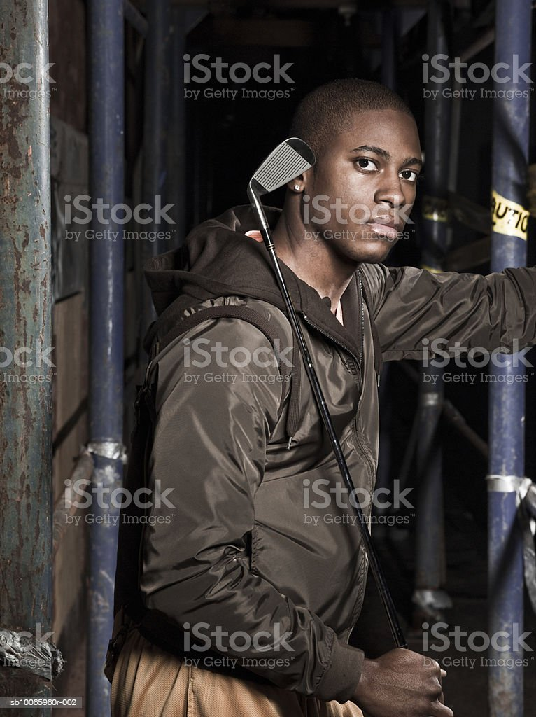 Young man holding golf club, portrait royalty-free stock photo