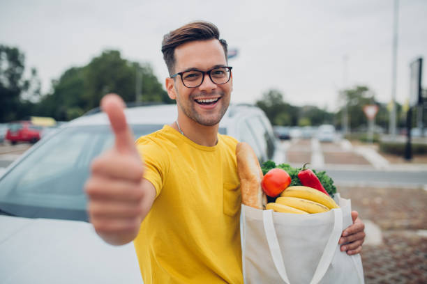 Young man holding groceries in reusable bag and showing thumb up stock photo