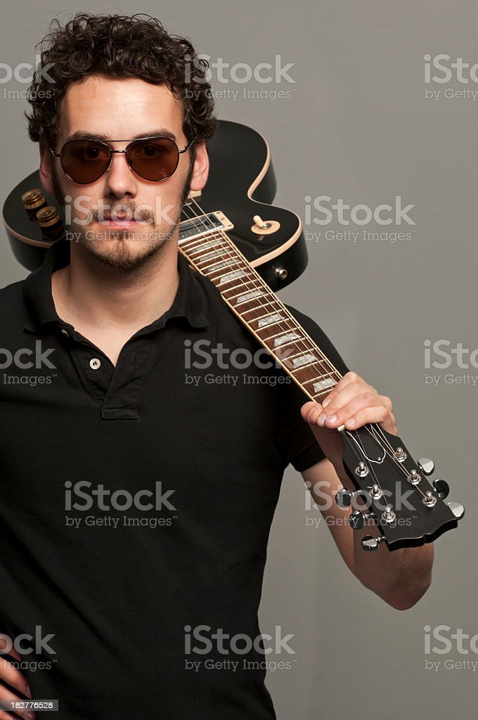 Young man holding guitar over shoulder wearing sunglasses stock photo