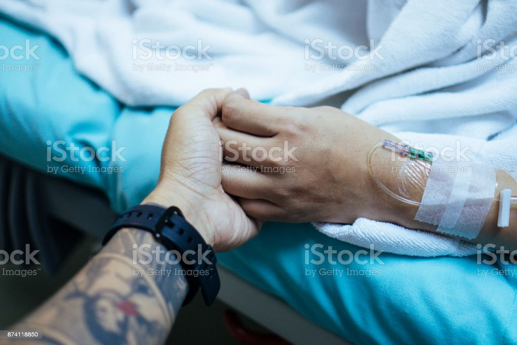 Young man holding hand of asian pregnant woman waiting in hospital bed stock photo