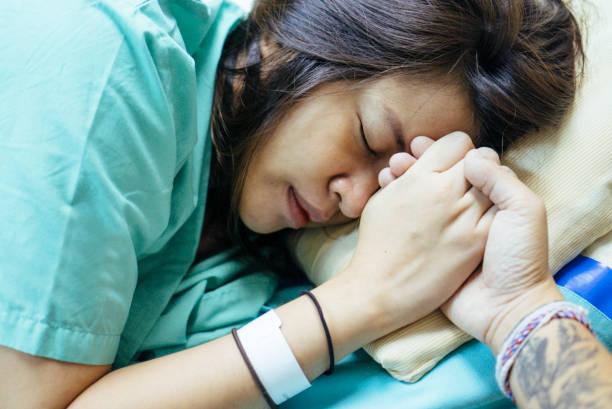 Jeune homme tenant la main de la femme enceinte asiatique attend dans son lit d'hôpital - Photo