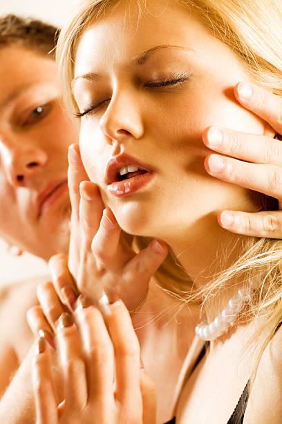 junger mann hält kopf der blonden frau, erotische - tantra massage stock-fotos und bilder
