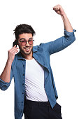 Casual young man holding his arm in the air while talking on the phone, isolated.