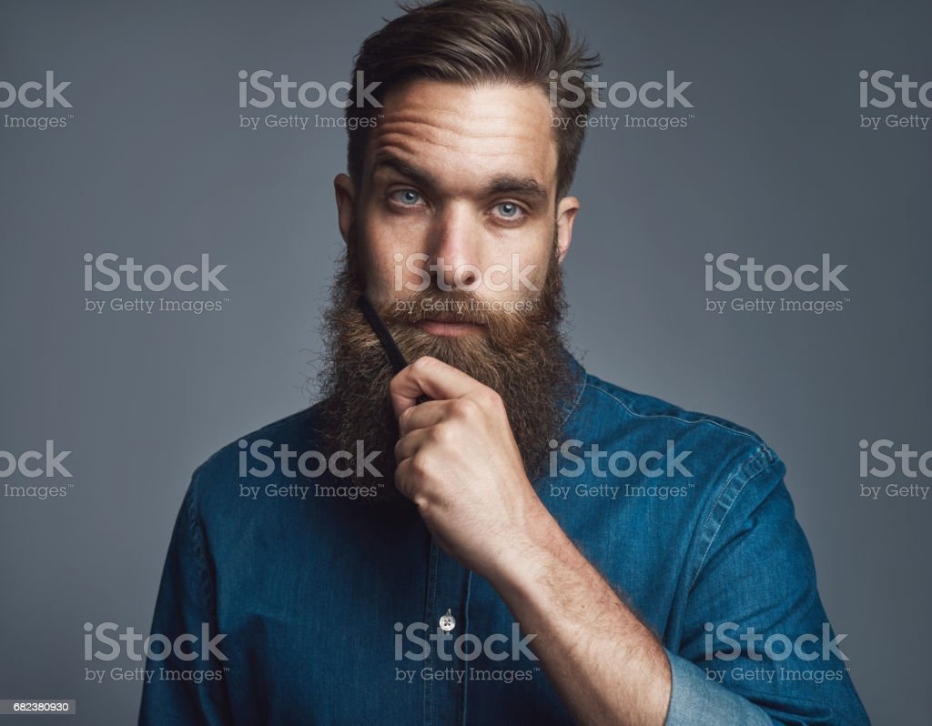 Young man holding his beard with blank stare stock photo