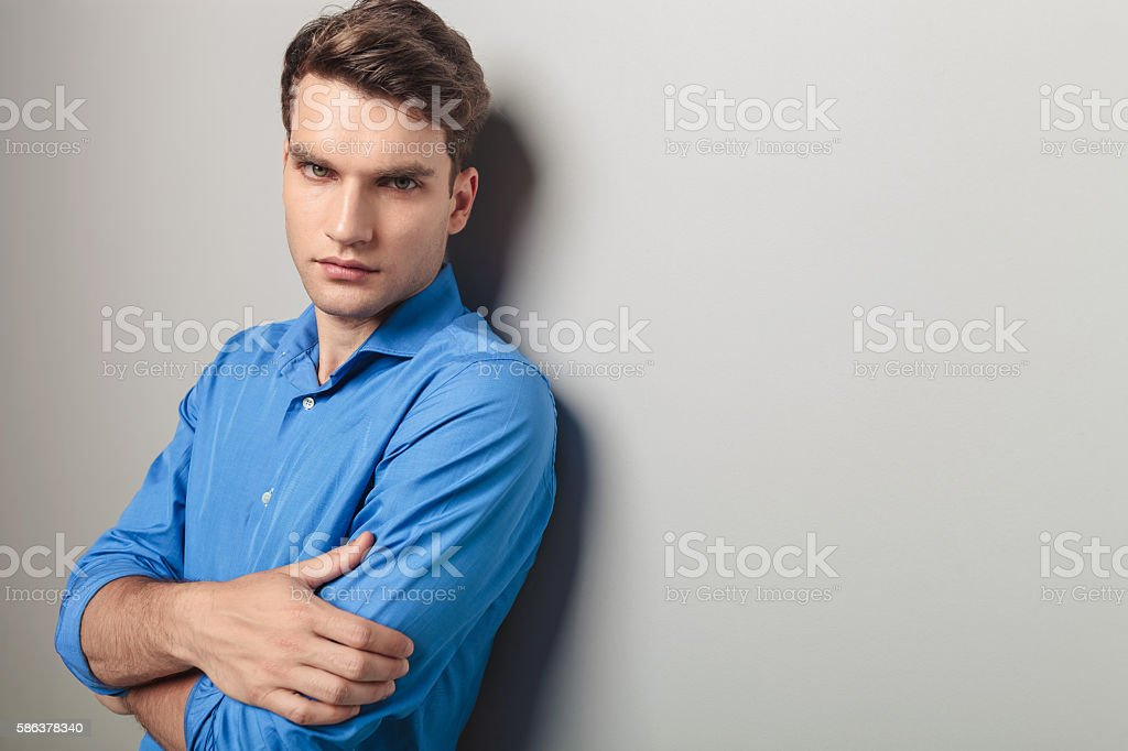 young man holding his hands crossed. stock photo