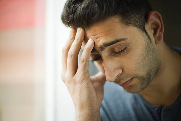 Young man holding his head out of headache near window. stock photo