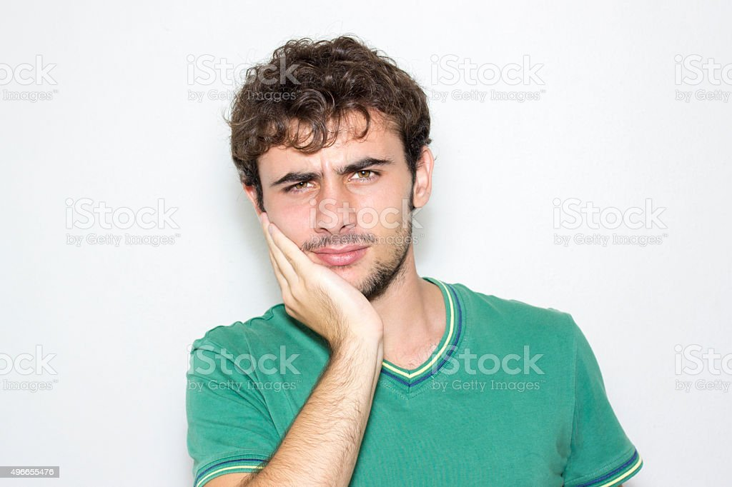 Young man holding his jaw in pain stock photo