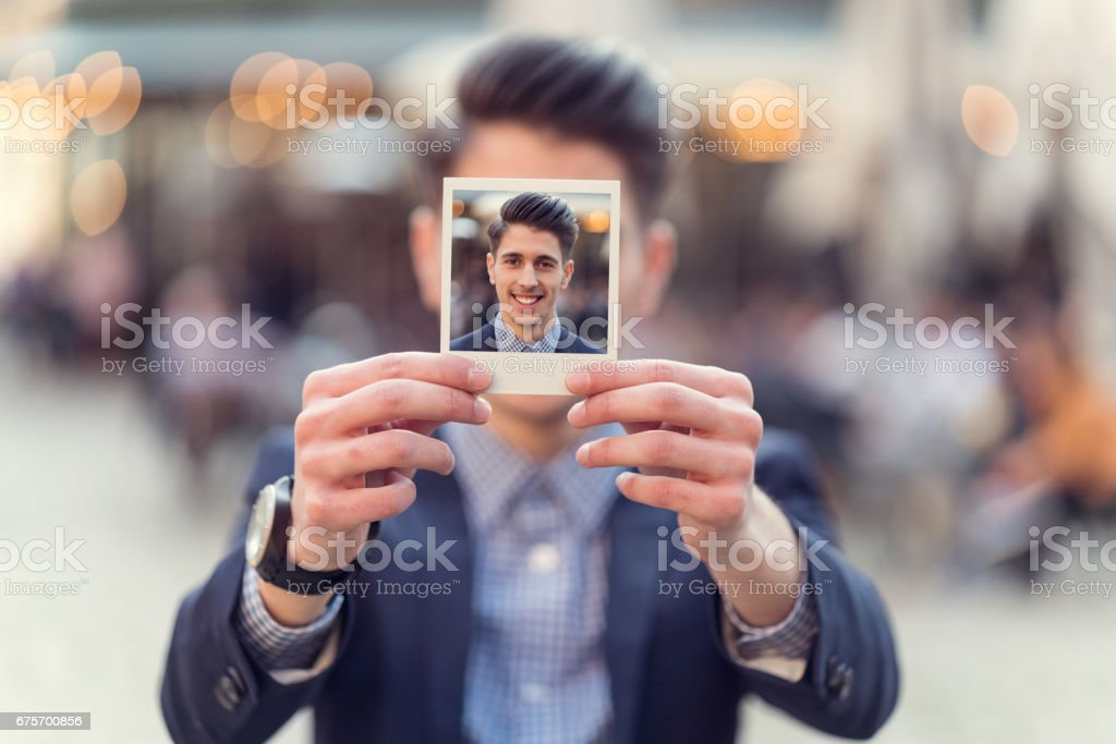 Young man holding instant photo in front of his face royalty-free stock photo