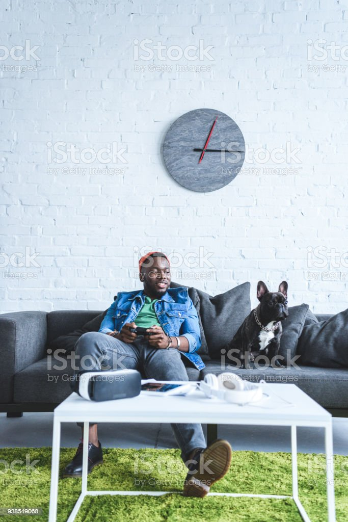 Young man holding joystick while sitting on sofa with bulldog and digital gadgets on table stock photo