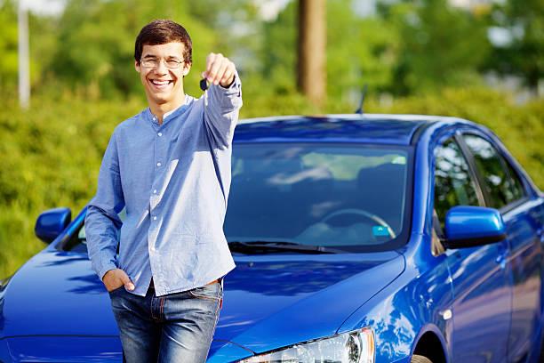 Junger Mann hält Schlüssel seines neuen Autos – Foto