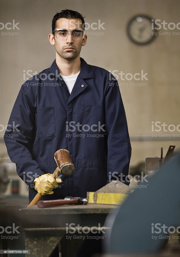 Young man holding mallet, portrait royalty free stockfoto