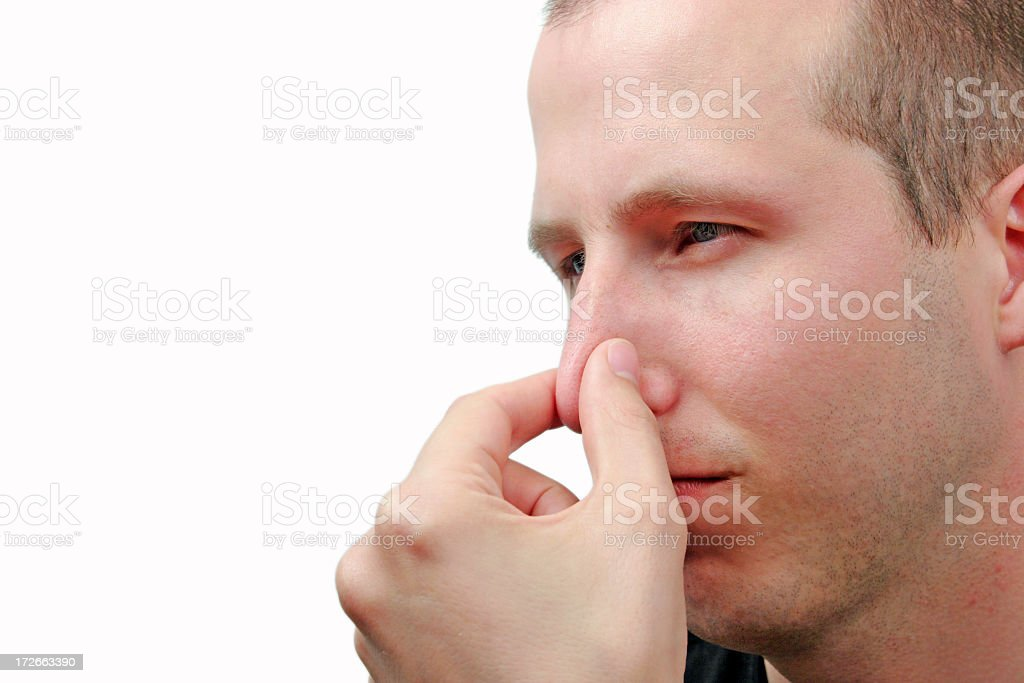 Young man holding nose to signify a bad smell royalty-free stock photo