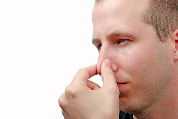 Young man holding nose to signify a bad smell stock photo