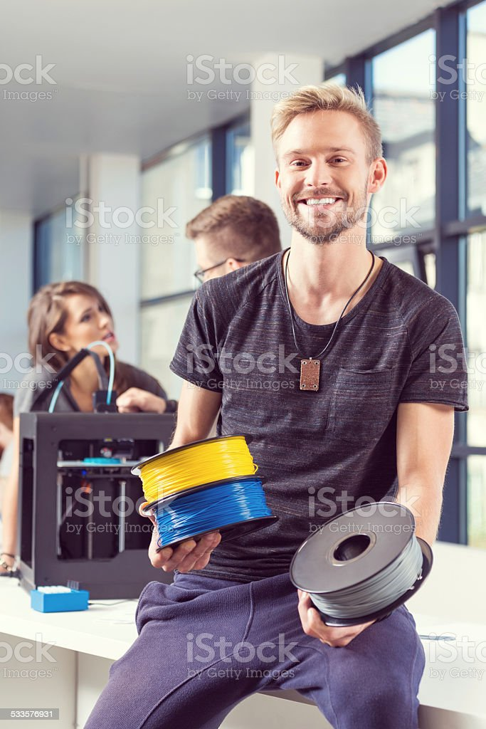 Young man holding plastic filaments in 3D printer office Young man holding plastic filaments in hands, smiling at the camera with people woking on 3D printer in the background.  2015 Stock Photo
