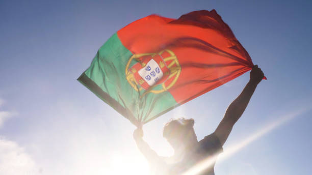 Young man holding portuguese national flag to the sky with two hands at the beach at sunset portugal stock photo
