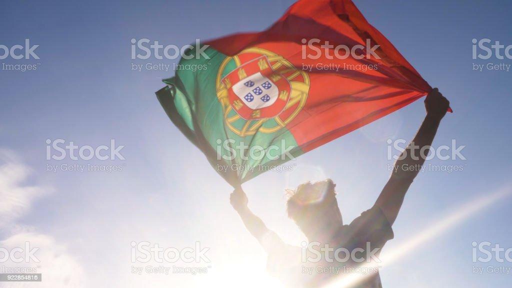 Joven sosteniendo la bandera nacional portuguéa al cielo con dos manos en la playa en portugal al atardecer - foto de stock