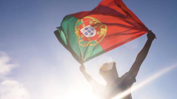 ung man håller portugisiska nationella flagga till himlen med två händer på stranden vid solnedgången portugal - football portugal flag bildbanksfoton och bilder