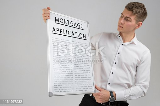 istock Young man holding poster with mortgage application isolated on light background 1134997232