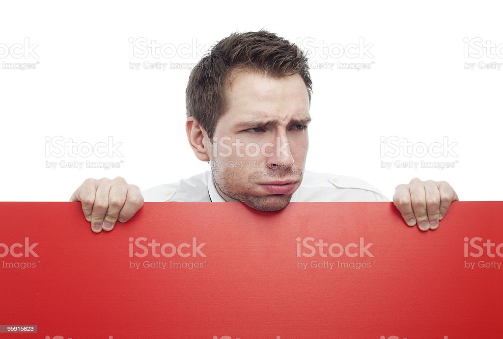 Young man holding red blank sigh sneering royalty-free stock photo
