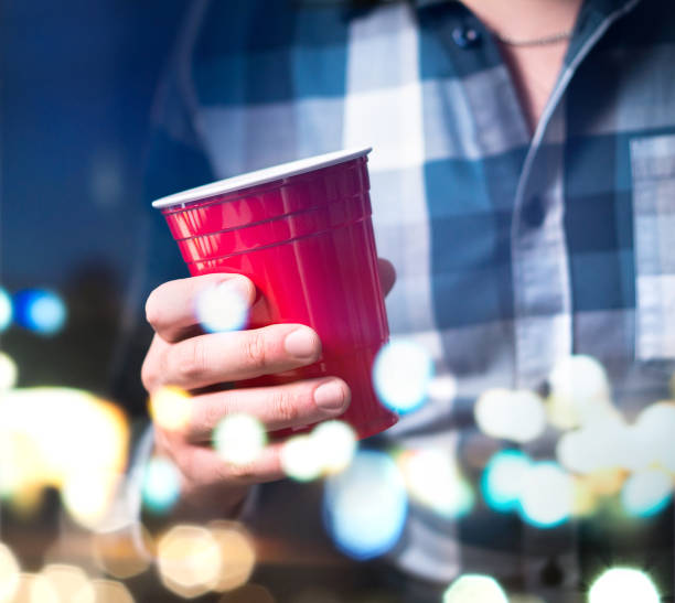junger mann halten rote tasse in einer luxus-party. person, spaß haben und alkohol zu trinken. - lustige trinkspiele stock-fotos und bilder