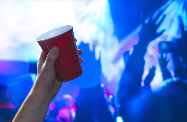 Young man holding red party cup in nightclub dance floor. Alcohol container in hand in disco. College student having fun and dancing. Celebrating people in the back. Event marketing and promotion. stock photo