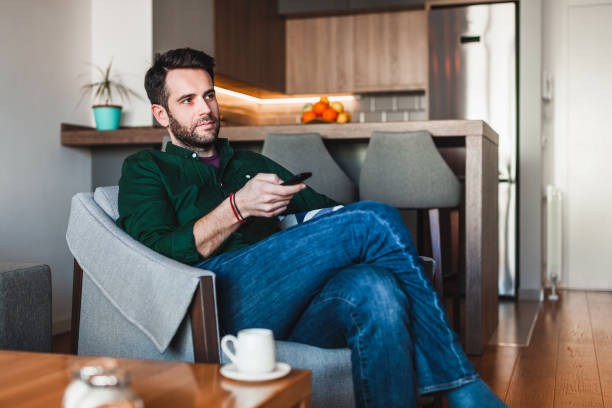Young man holding remote controller watching tv stock photo