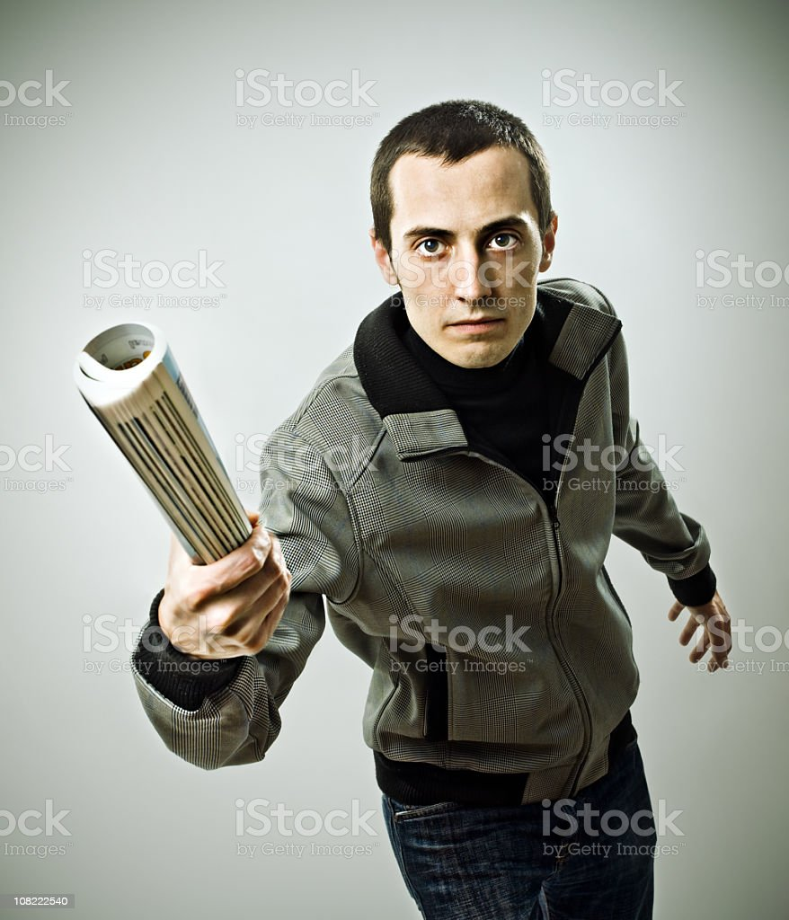 Young man holding rolled up newspaper royalty-free stock photo