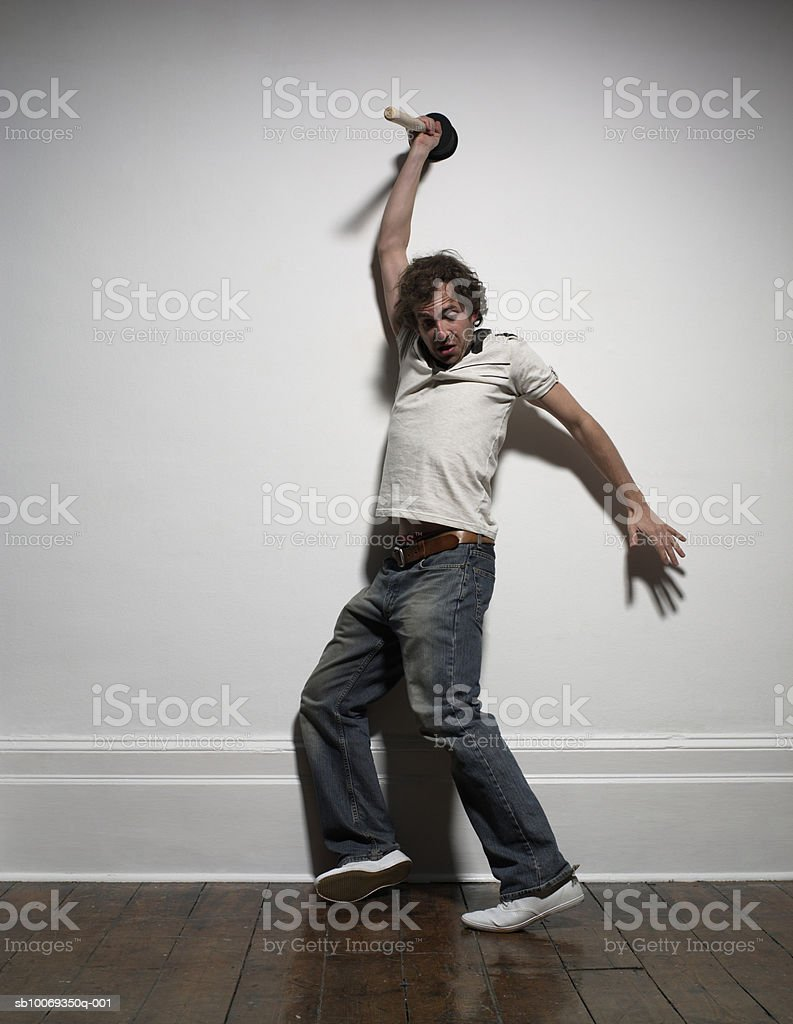 Young man holding sink plunger over head, indoors royalty-free stock photo